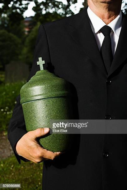 Mature man holding urn