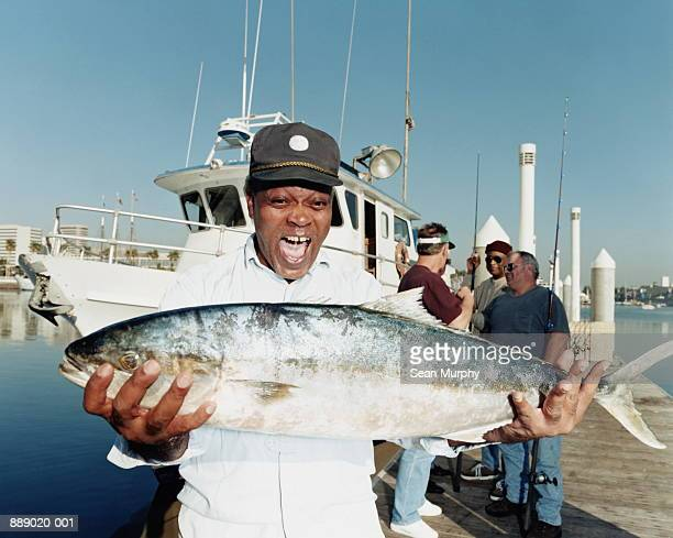 Mature man holding yellowtail fish on pier, boat in background