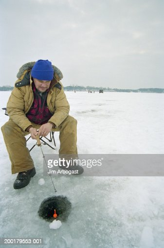 Mature man ice fishing on frozen lake stock photo getty for Frozen fishing pole