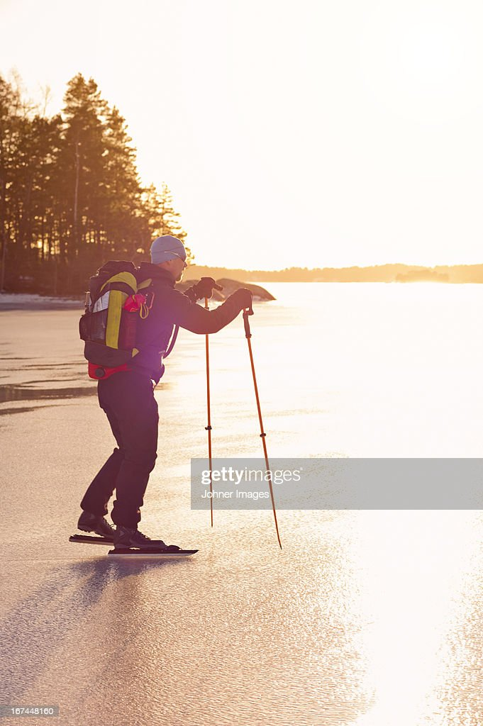 Mature man ice skating on frozen lake : Stock Photo