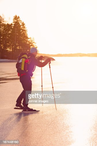 Mature man ice skating on frozen lake : Stock Photo