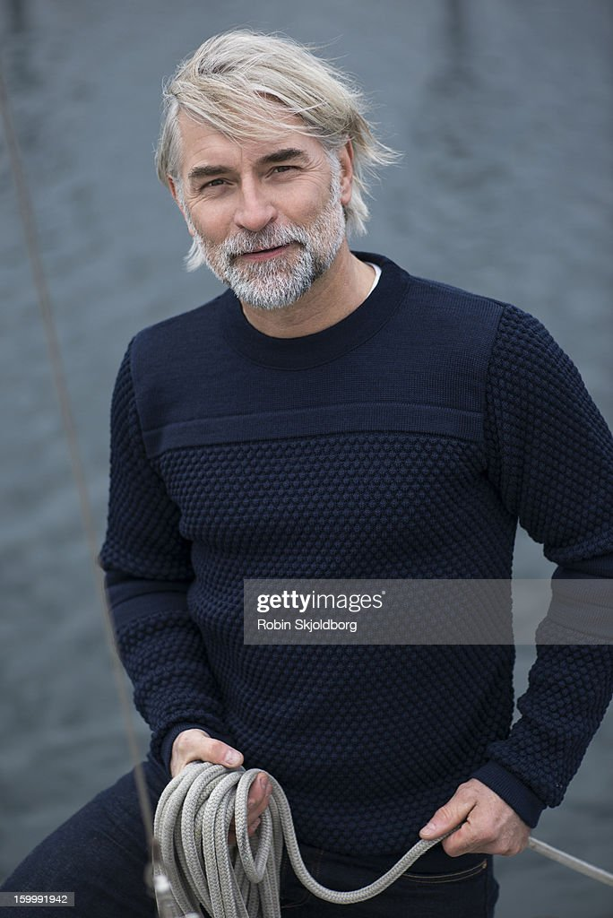 Mature man in blue sweater holding rope : Stock Photo