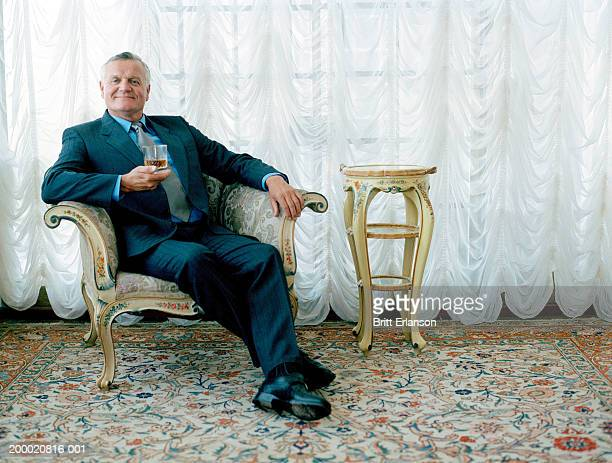 Mature man in chair holding drink, portrait
