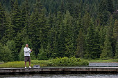 Mature man in distance, fishing from pier, forest in background