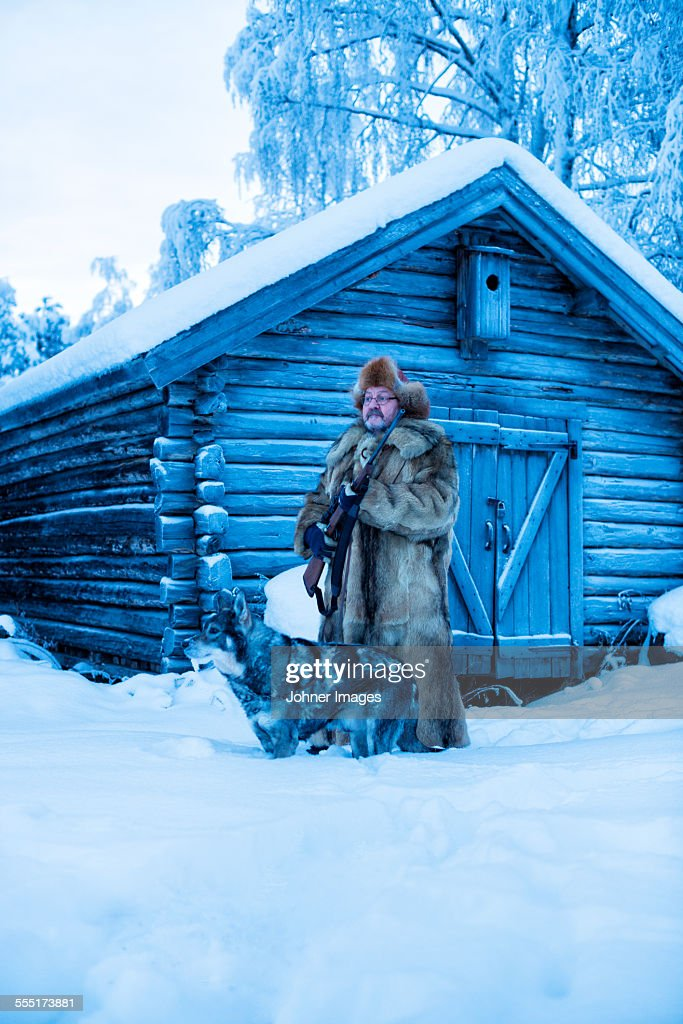 Mature man in front of log house