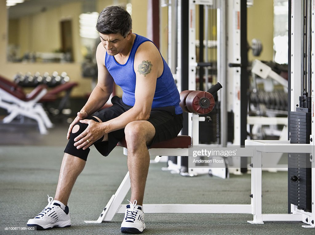 Mature man in gym wearing knee strap