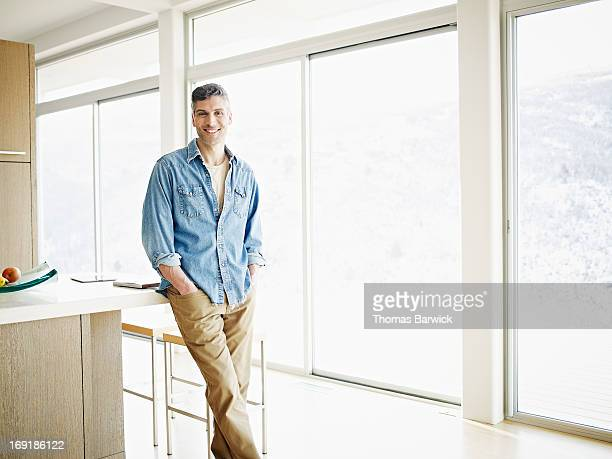 Mature man in kitchen in contemporary home smiling