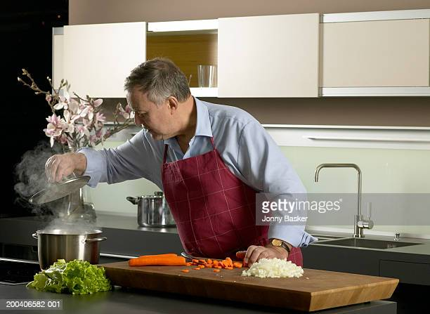 Mature man in kitchen lifting lid on saucepan emitting steam