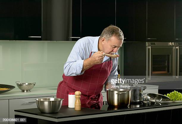 Mature man in kitchen tasting sauce