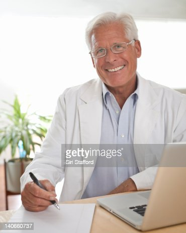 Mature man in lab coat working on laptop, smiling : Stock Photo