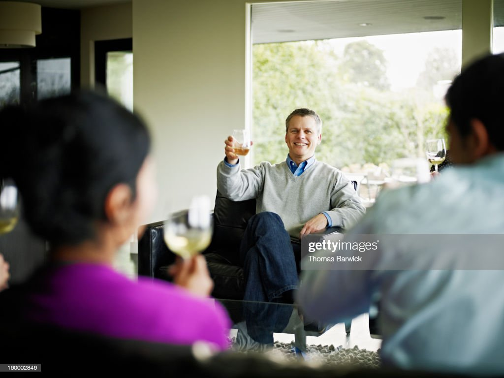 Mature man in living room giving toast : Stock Photo