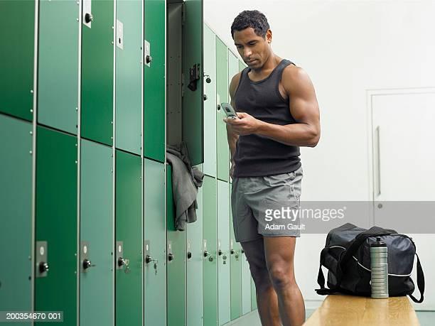 Mature man in locker room using mobile phone
