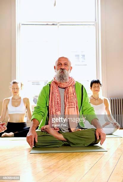 Mature man in lotus pose in yoga class