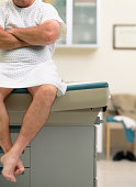Mature man in medical gown sitting on exam table, mid section