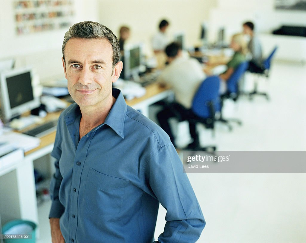 Mature man in office, hands on hips, smiling, portrait