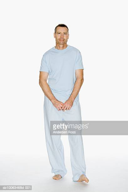 Mature man in pyjamas on white background, portrait