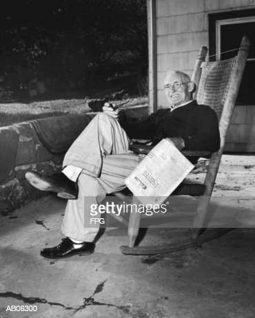 Mature man in rocking chair with pipe and newspaper (B&W) : Stock Photo