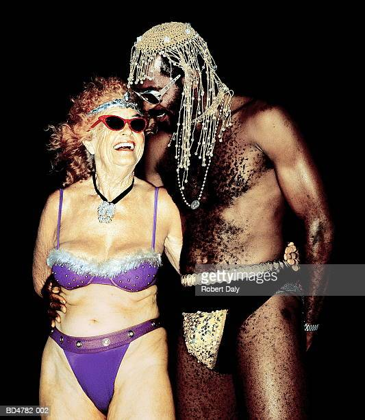 Mature man in sequinned codpiece, with elderly woman in bikini