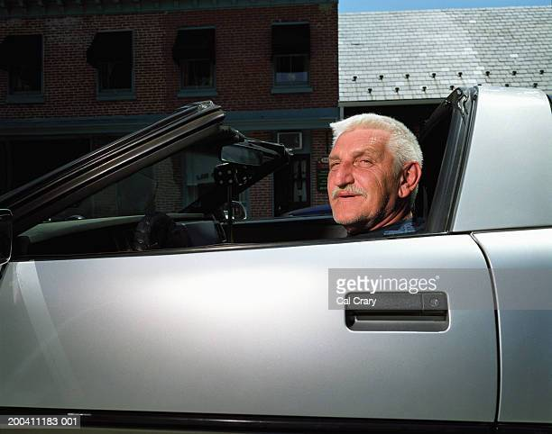 Mature man in sports car, portrait, side view, close-up