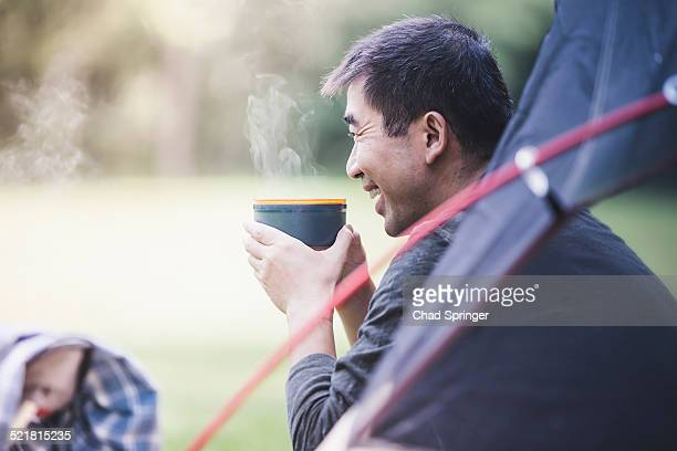 Mature man in tent with hot drink