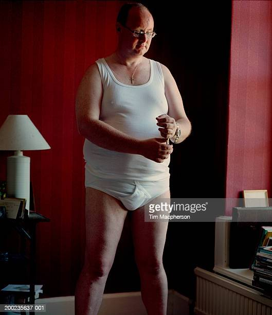 Mature man in underwear putting on watch