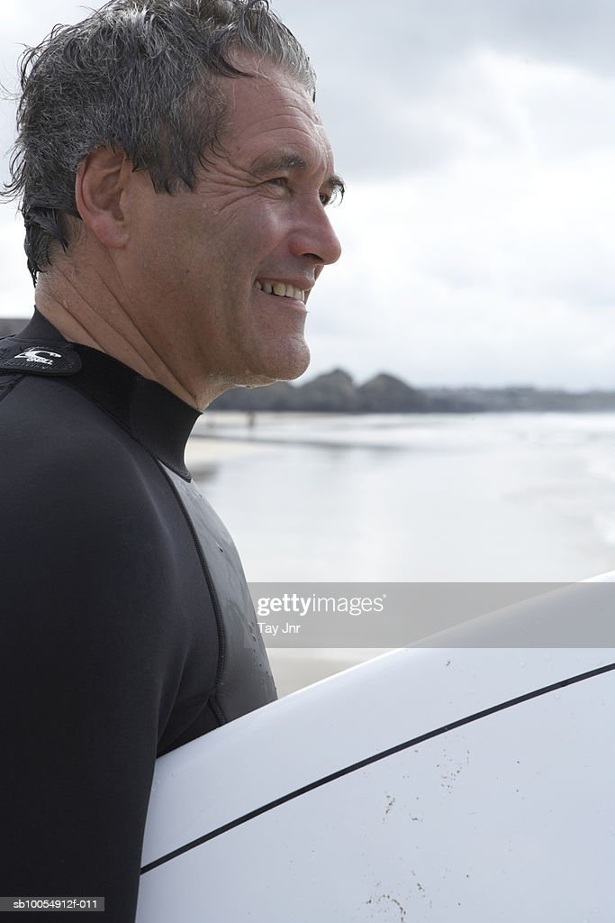 Mature man in wetsuit holding surfboard near sea, side view : Stock Photo