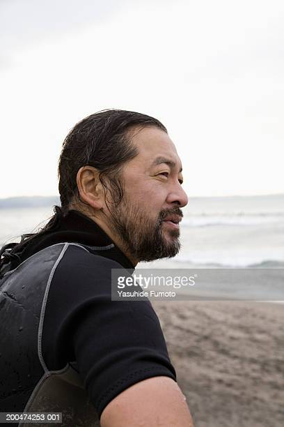 Mature man in wetsuit sitting on beach, side view