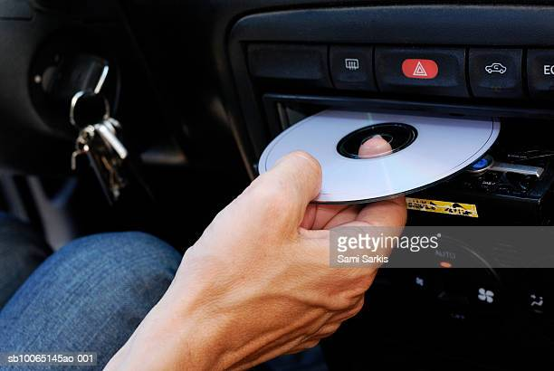 Mature man inserting compact disc into car stereo, close-up of hand