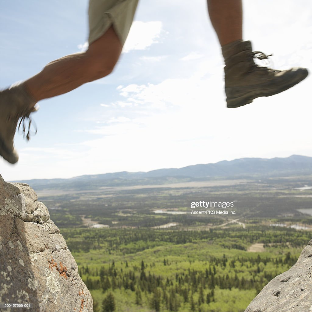Mature man jumping between two rocks, low section : Stock Photo