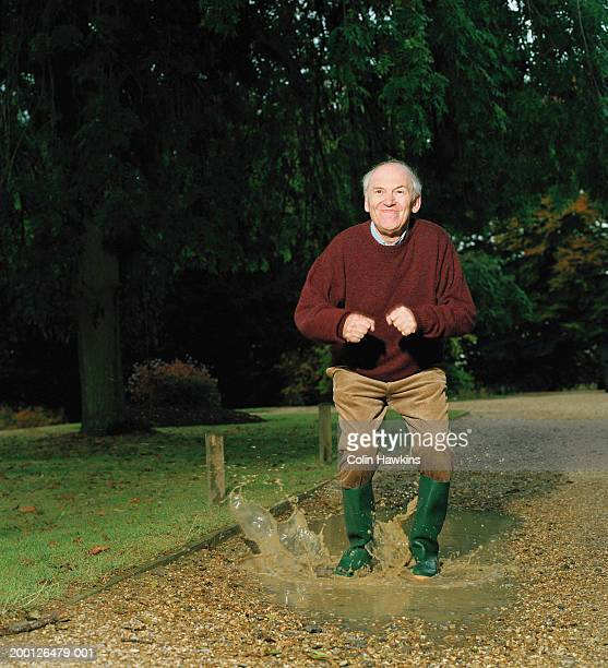 Mature man jumping in puddle