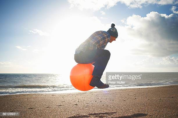 Mature man jumping mid air on inflatable hopper at beach