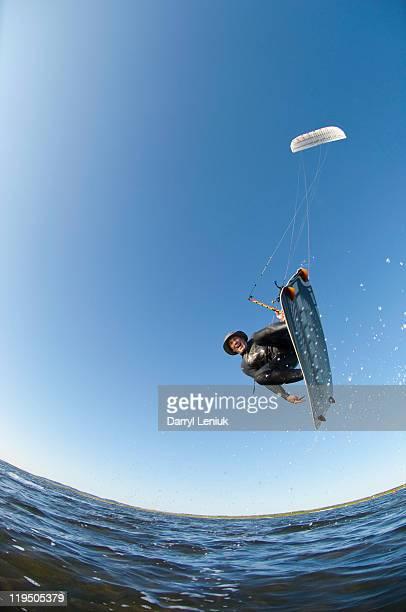 mature man jumping on kiteboard
