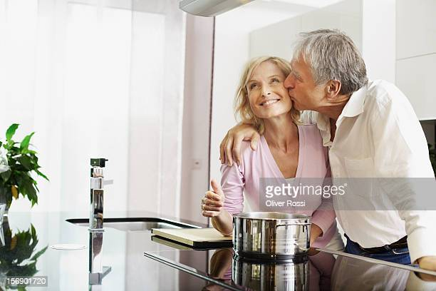 Mature man kissing wife in kitchen