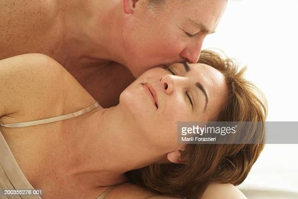 Mature man kissing woman, close-up