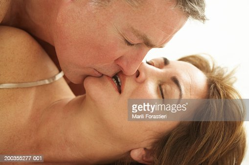 Mature man kissing woman, close-up : Stock Photo