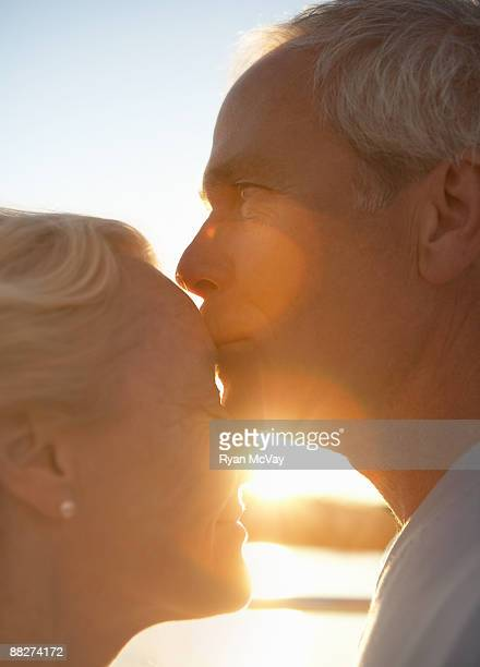 Mature man kissing woman on forehead