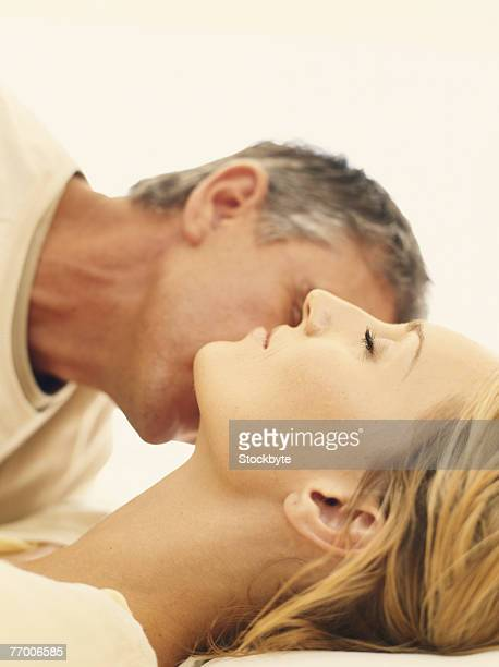 Mature man kissing woman's neck, side view, close-up