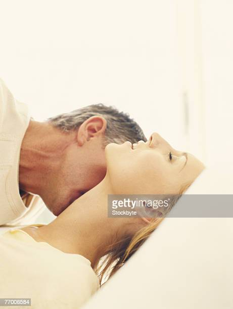 Mature man kissing woman's neck, side view