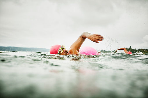 Mature man leading early morning open water swim