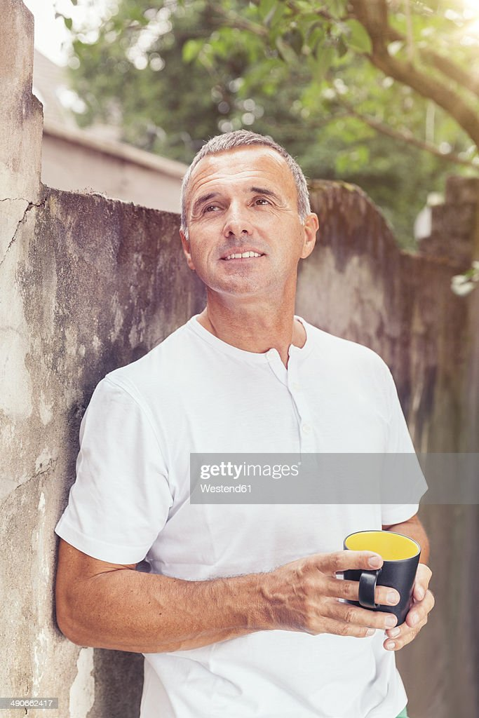 Mature man leaning against backyard wall with coffee cup in his hands
