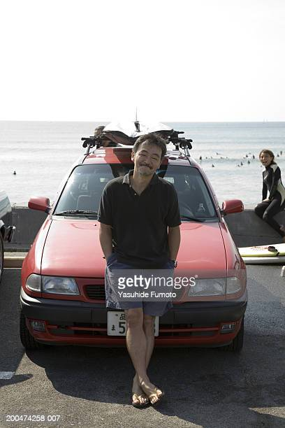 Mature man leaning against car, smiling, woman in background