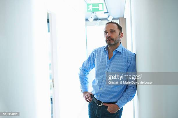 Mature man leaning against wall in corridor