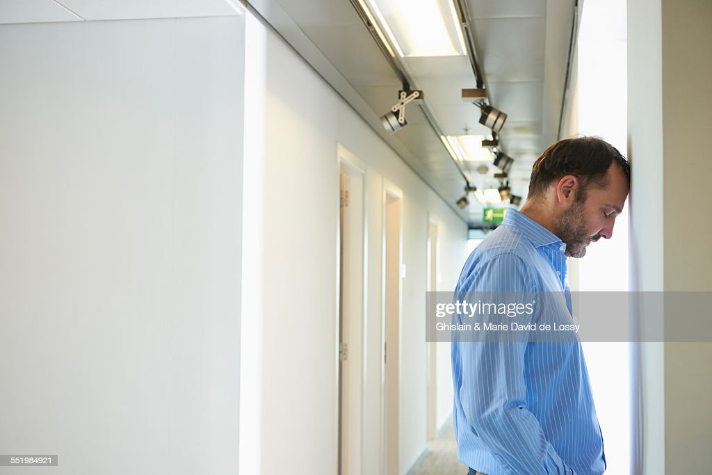 Mature man leaning head against wall in corridor