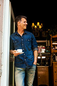 Mature man leaning in door of cafe, holding cup of coffee