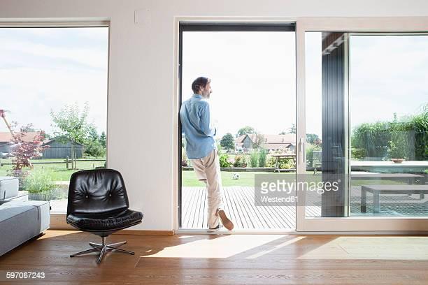 Mature man leaning in garden door, rear view