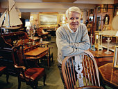 Mature man leaning on chair in antique shop, portrait