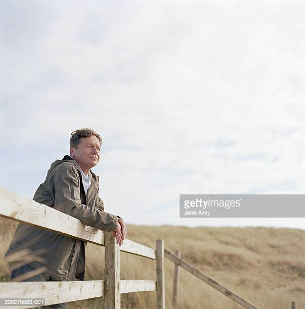 Mature man leaning on wooden rail outdoors