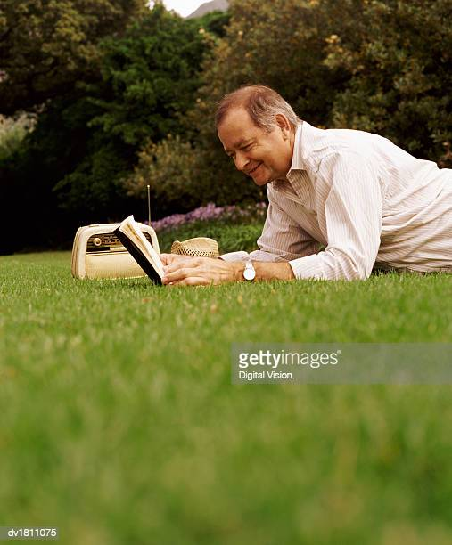 Mature Man Lies on the Grass Reading a Book and Listening to the Radio