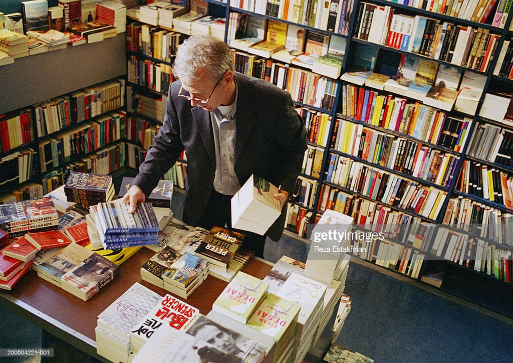 Mature man looking at books in bookstore : Stock Photo