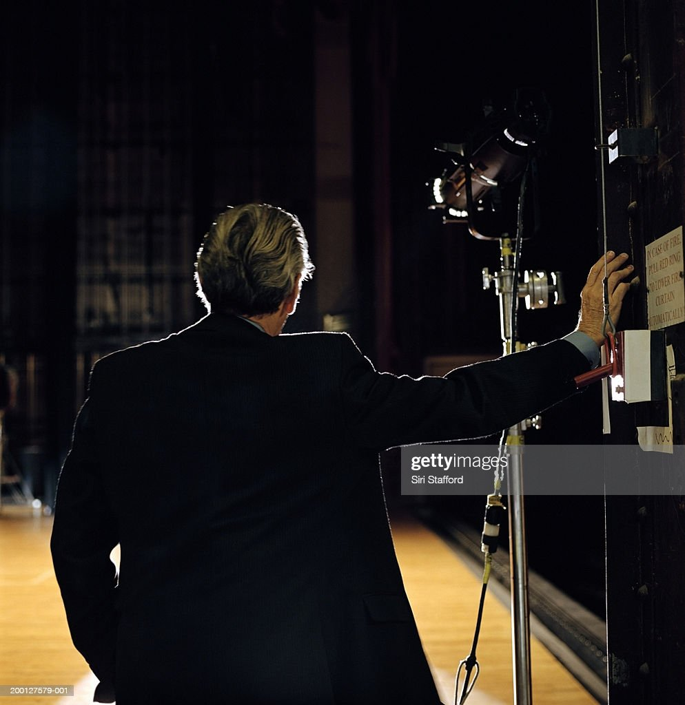 Mature man looking at empty stage, rear view : Stock Photo